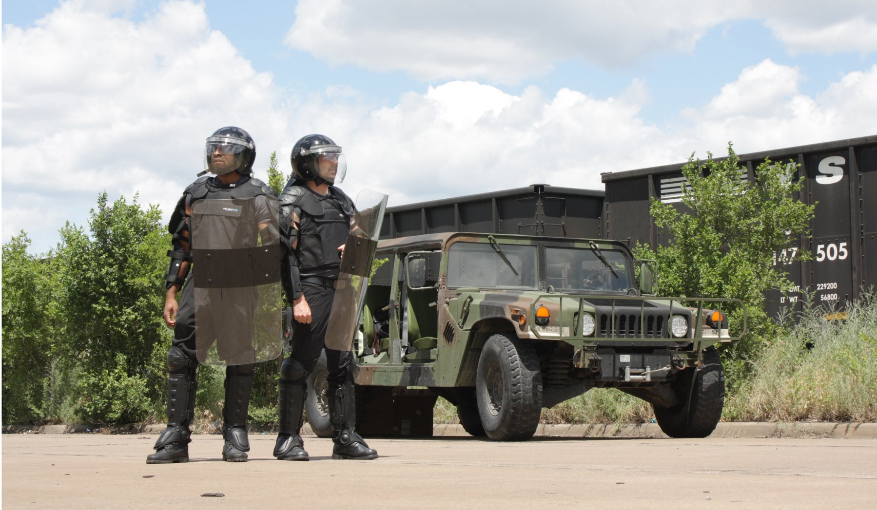 Two men standing near an army truck wearing a riot gear bundle