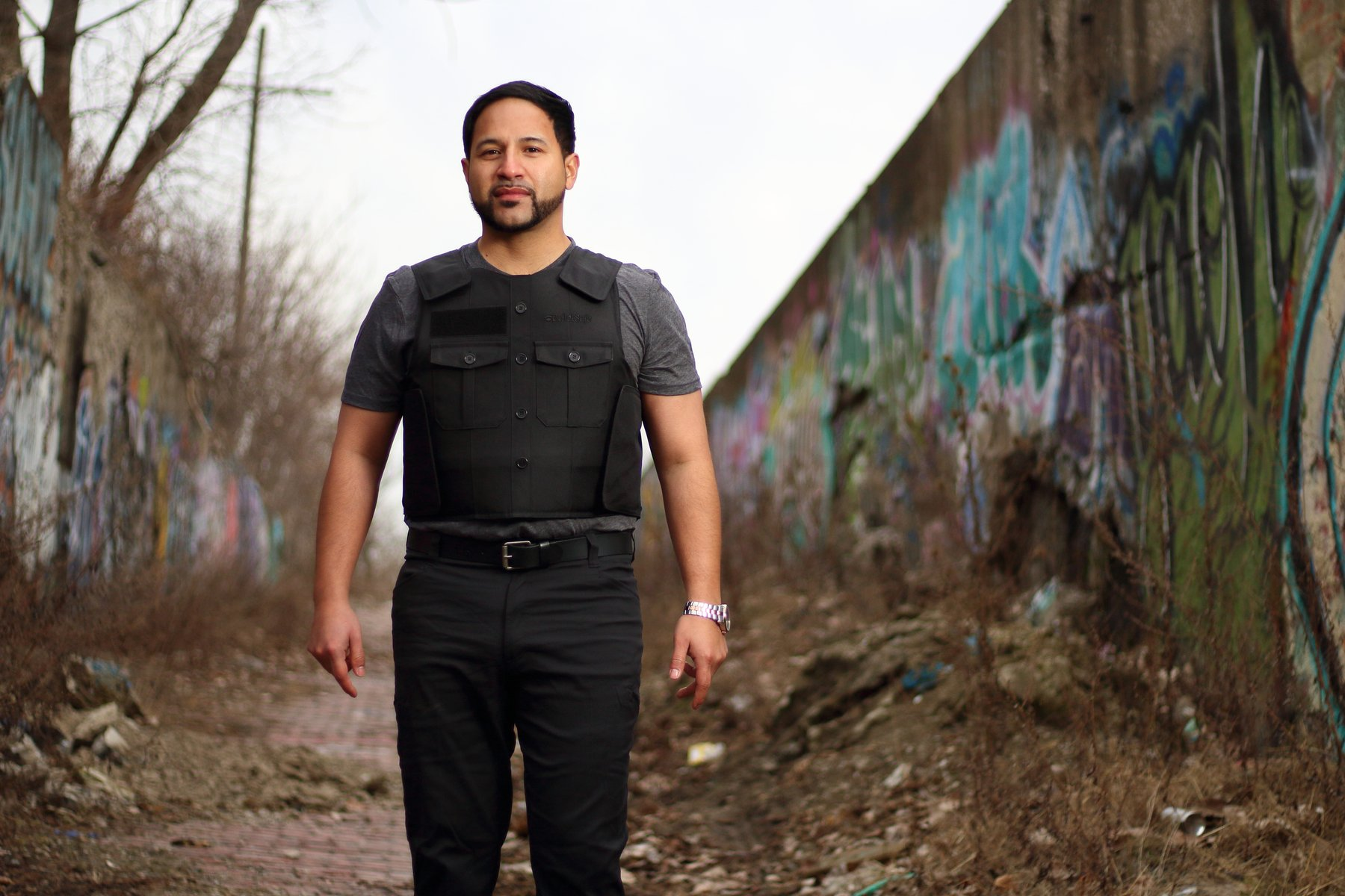A man standing straight while wearing a bulletproof vest