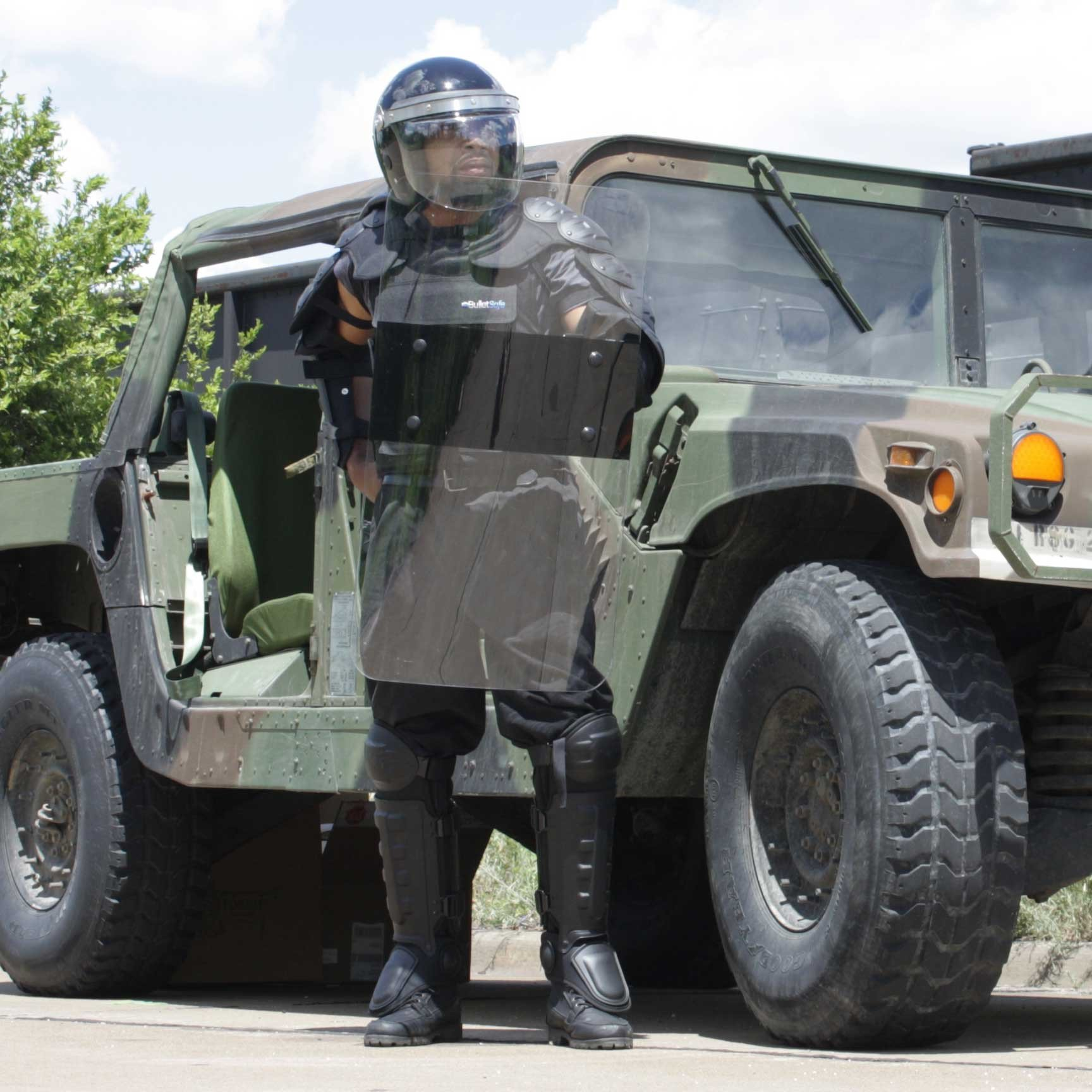 A man standing beside an army truck wearing a riot gear bundle