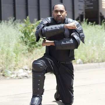 Man on one knee wearing RiotReady body armor arm, shoulder, and leg pads