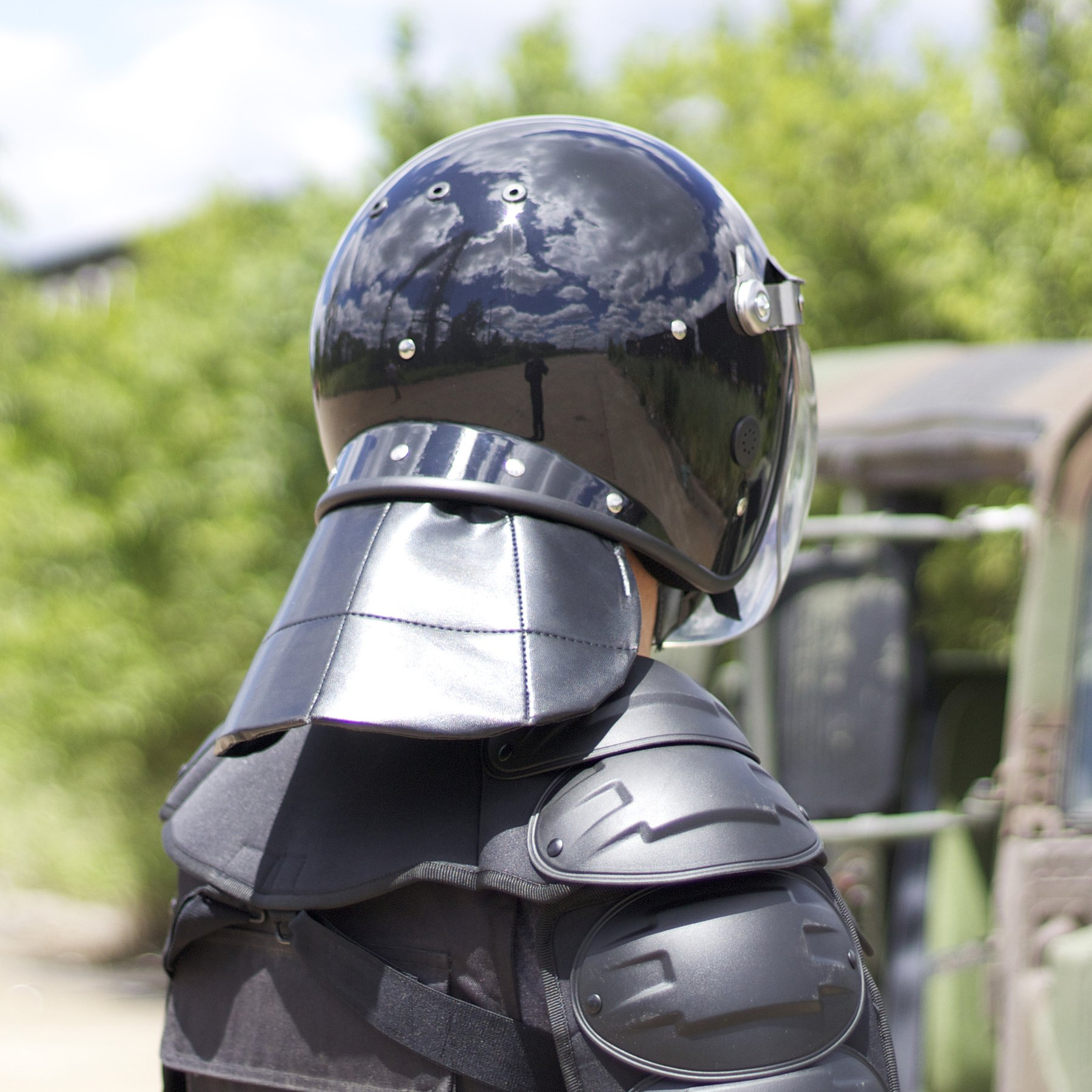 A man standing beside an army truck holding a RiotReady riot shield