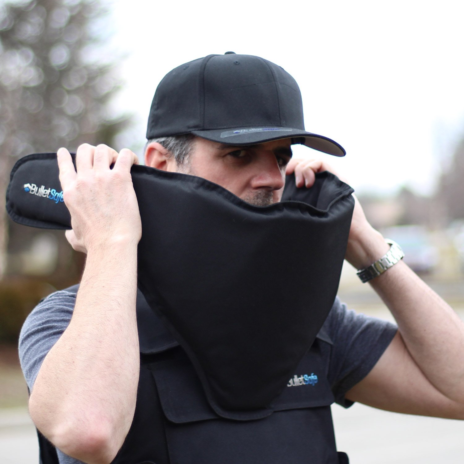 A man in a cap putting a bulletproof bandana around his face and neck